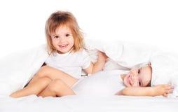 Lyckliga små flickor kopplar samman systern i säng under filten som har gyckel Royaltyfri Fotografi