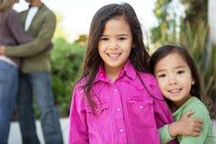 Lyckliga små flickor med deras föräldrar i bakgrunden Arkivfoto