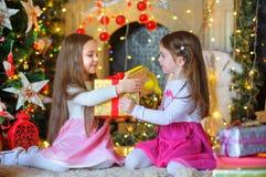 Lyckliga små flickor med en gåva i händer Fotografering för Bildbyråer