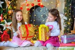 Lyckliga små flickor med en gåva i händer Arkivfoto