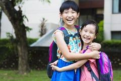 Lyckliga små flickor med klasskompisar som har gyckel på skolan royaltyfria bilder