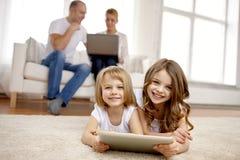 Lyckliga små flickor med minnestavlaPCdatoren hemma Royaltyfri Foto