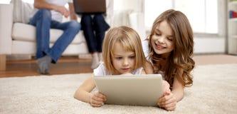 Lyckliga små flickor med minnestavlaPCdatoren hemma Arkivfoton