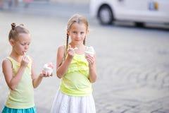 Lyckliga små flickor som äter det frilufts- kafét för is-creamin Folk, barn, vänner och kamratskapbegrepp Arkivfoto