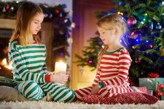 Lyckliga små flickor som bär julpyjamas som spelar vid en spis i en hemtrevlig mörk vardagsrum på julhelgdagsafton royaltyfria bilder