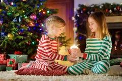 Lyckliga små flickor som bär julpyjamas som spelar vid en spis i en hemtrevlig mörk vardagsrum på julhelgdagsafton royaltyfri foto
