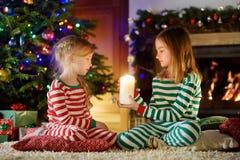 Lyckliga små flickor som bär julpyjamas som spelar vid en spis i en hemtrevlig mörk vardagsrum på julhelgdagsafton arkivfoto