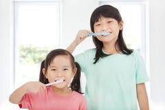 Lyckliga små flickor som borstar hennes tänder Arkivfoto