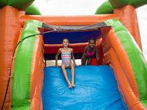 Lyckliga små flickor som glider ner ett uppblåsbart dunshus Royaltyfria Foton