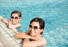 Lyckliga små flickor som har gyckel i simbassäng arkivbilder