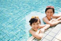 Lyckliga små flickor som har gyckel i simbassäng royaltyfri bild