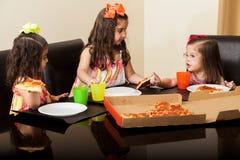 Lyckliga små flickor som har någon pizza Arkivbilder