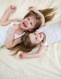 Lyckliga små flickor som ligger på baksida från över royaltyfria foton
