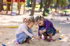 Lyckliga små flickor som spelar i en sendbox Royaltyfri Foto