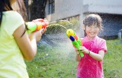 Lyckliga små flickor som spelar vattenvapen i parkera Arkivfoton