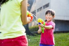 Lyckliga små flickor som spelar vattenvapen i parkera Royaltyfri Foto