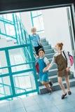 lyckliga små klasskompisar som går ner trappa royaltyfri bild