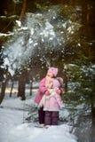 Lyckliga små systrar har gyckel i snöig skog royaltyfria bilder