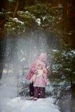Lyckliga små systrar har gyckel i snöig skog arkivbilder