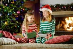 Lyckliga små systrar som bär julpyjamas som öppnar gåvaaskar vid en spis i en hemtrevlig mörk vardagsrum på julhelgdagsafton royaltyfri foto