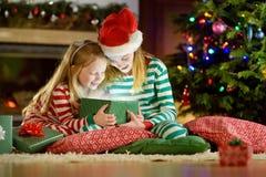 Lyckliga små systrar som bär julpyjamas som öppnar gåvaaskar vid en spis i en hemtrevlig mörk vardagsrum på julhelgdagsafton royaltyfri fotografi