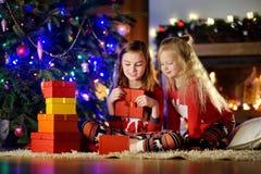 Lyckliga små systrar som bär julpyjamas som spelar vid en spis i en hemtrevlig mörk vardagsrum på julhelgdagsafton Royaltyfri Foto