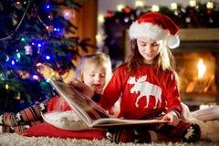Lyckliga små systrar som läser en berättelse, bokar tillsammans vid en spis i en hemtrevlig mörk vardagsrum på julhelgdagsafton fotografering för bildbyråer