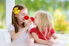 Lyckliga små systrar som tillsammans bär röda clownnäsor som har gyckel på solig sommardag hemma Royaltyfria Bilder