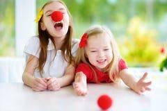 Lyckliga små systrar som tillsammans bär röda clownnäsor som har gyckel på solig sommardag hemma Arkivbilder