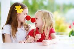 Lyckliga små systrar som tillsammans bär röda clownnäsor som har gyckel på solig sommardag hemma Arkivfoto