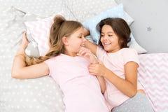 Lyckliga små ungar för systrar som kopplar av i sovrum kamratskap av små flickor Fritid och gyckel Ha gyckel med bästa vän royaltyfri foto