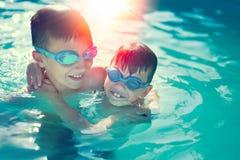 Lyckliga små ungar har gyckel i den graderade simbassängen fotografering för bildbyråer