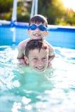 Lyckliga små ungar har gyckel i simbassäng Royaltyfria Foton