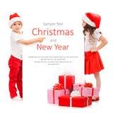Lyckliga små ungar i jultomtenhatt som bakifrån kikar Arkivfoto