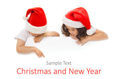 Lyckliga små ungar i jultomtenhatt som bakifrån kikar Royaltyfri Foto