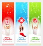 Lyckliga små ungar i jultomtenhatt som bakifrån kikar Arkivbild