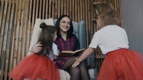 Lyckliga små ungar omfamnar deras tillgivna moder som rymmer boken i hans hand och sitter på stolen bredvid väggen arkivfilmer