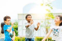 Lyckliga små ungar som blåser såpbubblor i sommar, parkerar Unge och vänner i internationell förskole- lek en bubbla royaltyfri bild