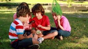 Lyckliga små vänner som ser kruset lager videofilmer