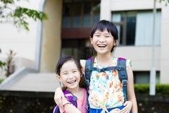 Lyckliga små flickor med klasskompisar som har gyckel på skolan Royaltyfria Foton