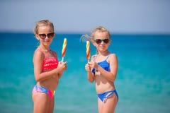 Lyckliga små flickor som äter glass på stranden Royaltyfri Foto