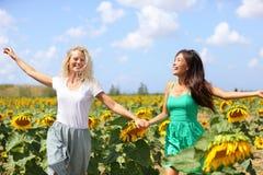 Lyckliga sommarflickor som skrattar gyckel i solrosfält Royaltyfria Foton