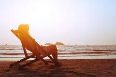 Lyckliga sommarstrandferier kvinna som kopplar av i deckchair, tropisk semester arkivfoton
