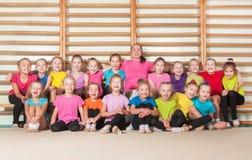 Lyckliga sportiga barn i idrottshall arkivfoto