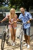 Lyckliga sportiga tillfälliga par som går för cykel, rider Royaltyfri Fotografi