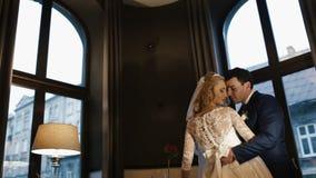 Lyckliga stilfulla nygifta personer är krama och kyssa slappt i den moderna restaurangen arkivfilmer