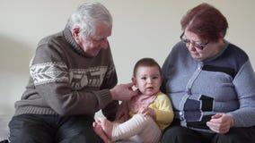 Lyckliga storslagna morföräldrar som lite spelar med lilla barnet petig hemmastadd 4k arkivfilmer