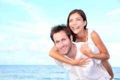 Lyckliga strandpar på ryggen Royaltyfria Foton