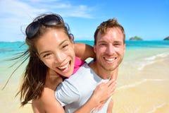 Lyckliga strandpar som är förälskade på sommarsemestrar Arkivfoto