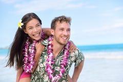Lyckliga strandpar som har rolig piggybacking Arkivbild